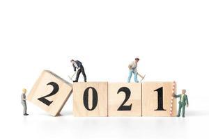 Groupe de travailleurs miniatures équipe avec des blocs en bois avec numéros 2021