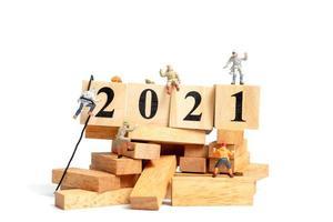 Groupe de personnes miniatures grimpant sur des cubes en bois avec des numéros 2021