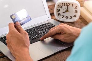 personne utilisant une carte de crédit pour faire des achats en ligne via un ordinateur photo