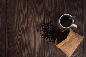 tasse à café avec des grains de café sur une table en bois