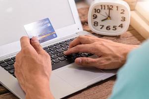 les gens utilisent des cartes de crédit pour faire des achats en ligne sur des ordinateurs portables photo