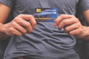 un homme tenant une carte de crédit à la main