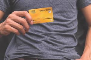 un homme tenant une carte de crédit sur sa main