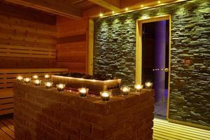 sauna moderne avec bougies et intérieur en pierre