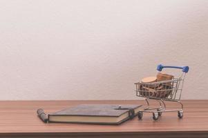 Ordinateur portable sur le bureau avec des pièces dans un petit chariot photo