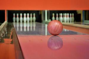 boule de bowling rouge sur la piste dans le centre de bowling photo