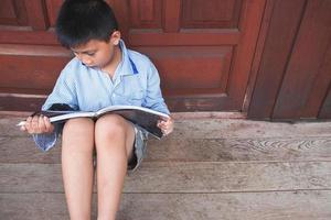 Garçon assis contre la porte en bois en lisant un livre sur le plancher en bois photo