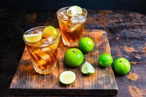 Thé glacé et tranches de citron vert sur un plateau en bois sur une table en bois photo