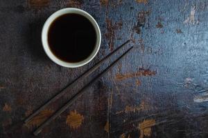 Tasse de sauce soja avec une paire de baguettes sur un fond de bois foncé photo