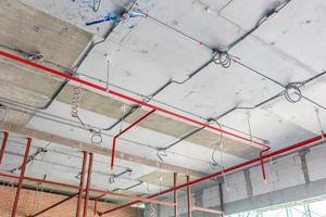 Tuyaux de ventilation en matériau isolant et gicleurs d'incendie sur tuyau rouge