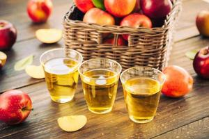 jus de pomme dans des verres et pommes dans le panier