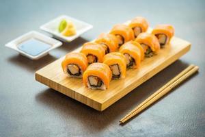 Rouleaux de sushi au saumon sur plaque de bois photo