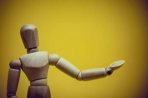 mannequin en bois présentant un objet invisible