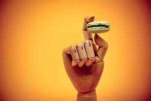 main en bois tenant le macaron