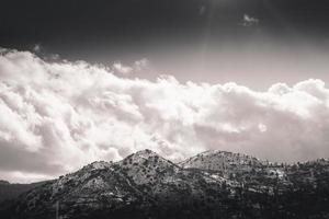 Sommet de la montagne enneigée contre ciel nuageux photo