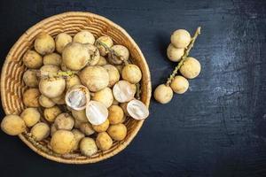 Longkong ou langsat fruits dans un panier en osier sur un fond de bois noir