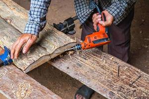 L'homme à l'aide d'une perceuse électrique sur planche de bois dans un atelier de menuiserie