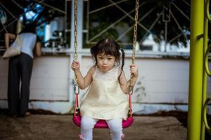 jeune fille se balançant dans un parc photo