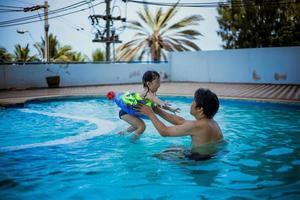 père et fille jouant dans une piscine photo