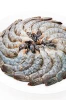 Crevettes fraîches crues sur une assiette blanche
