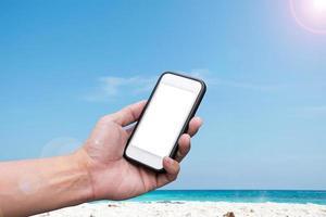 main tenant un smartphone sur une plage et un fond de ciel bleu