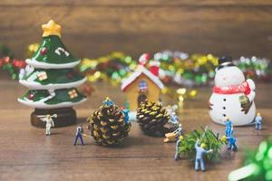 Personnes miniatures créant des décorations de Noël sur un fond de bois photo