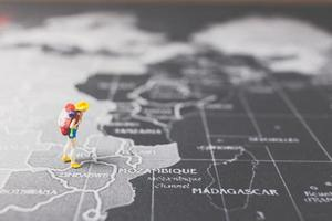 Routard miniature marchant sur une carte du monde, concept de tourisme et de voyage