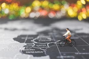 voyageur miniature, faire du vélo sur une carte du monde, voyager et explorer le concept du monde