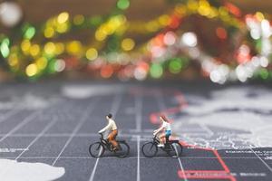 voyageurs miniatures à vélo sur une carte du monde, voyageant et explorant le concept du monde