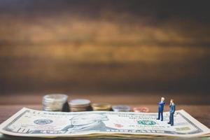 Hommes d'affaires miniatures sur de l'argent sur un fond de bois