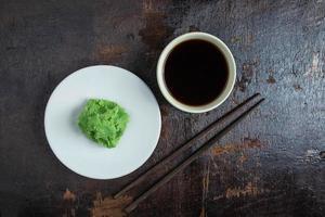 Sauce soja dans une tasse blanche et wasabi sur une plaque blanche sur un fond en bois noir photo
