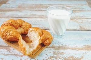 Croissants sur une planche à découper en bois à côté d'un verre de lait sur une table en bois bleu photo