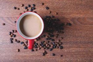 Café dans une tasse de café rouge à côté de grains de café renversés sur une table en bois