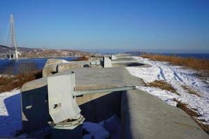 Vue paysage de la batterie Voroshilov et le pont Russky contre un ciel bleu clair à Vladivostok, Russie photo