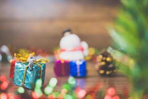 Personne miniature sur une boîte-cadeau avec décoration de fête de Noël en arrière-plan photo