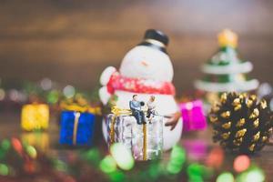personnes miniatures sur une boîte-cadeau avec décoration de fête de Noël en arrière-plan photo