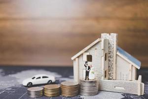 mariée et le marié miniature avec des pièces devant une maison, concept de famille réussie photo