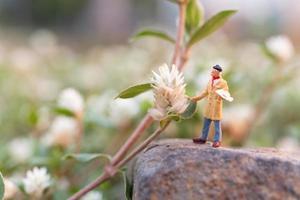 Artiste miniature tenant un pinceau et peignant des fleurs dans le jardin