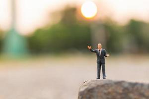 Homme politique miniature s'exprimant sur une falaise rocheuse