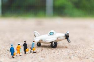 Voyageurs miniatures tenant un bagage à main dans un avion, explorant le concept du monde