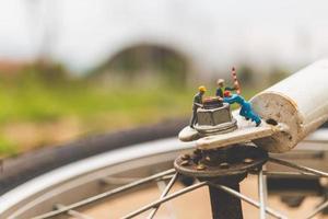 Mécanique miniature réparant un vélo, concept d'atelier photo