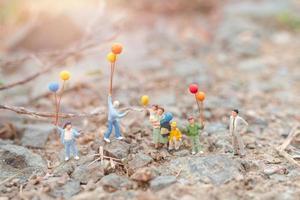 Famille miniature marchant dans un champ avec des ballons, concept de temps en famille heureuse photo