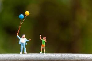 famille miniature tenant des ballons colorés, concept de famille heureuse photo