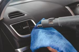 personne nettoyant une voiture à la vapeur photo
