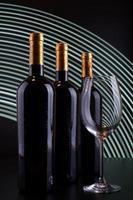 bouteilles de vin et verre avec fond de lignes blanches photo