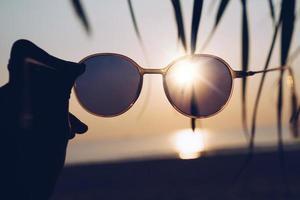 femme tient des lunettes de soleil sur fond d'été plage coucher de soleil photo