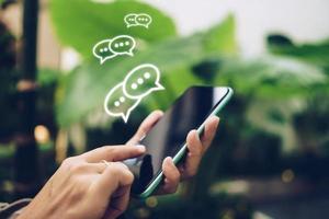 personne utilisant un smartphone avec des icônes de saisie, de discussion ou d'envoi de SMS