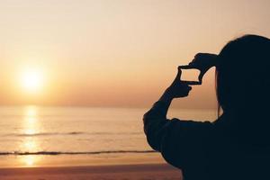 mise au point sélective des mains de la femme faisant le cadre avec le lever du soleil