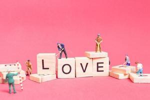 Travailleurs miniatures construisant le mot amour sur des blocs de bois avec un fond rose, concept de la Saint-Valentin