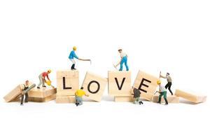 Travailleurs miniatures construisant le mot amour sur des blocs de bois avec un fond blanc, concept de la Saint-Valentin photo